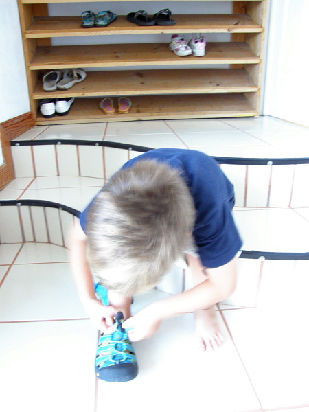 Boy putting on shoes.