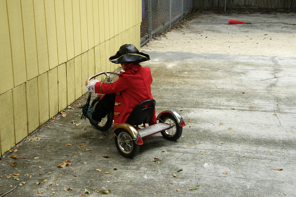 Boy in pirate costume parking a tricycle