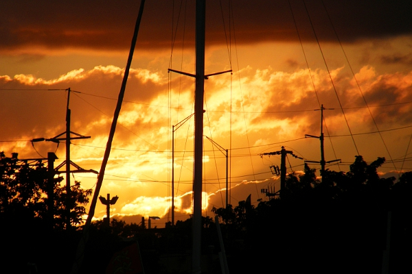 Sailboat mast and rigging, powerlines, light poles at sunset