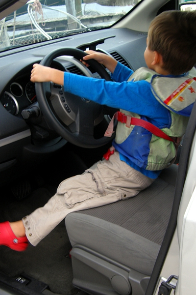 Boy in life vest sitting behind the wheel of a rental car.