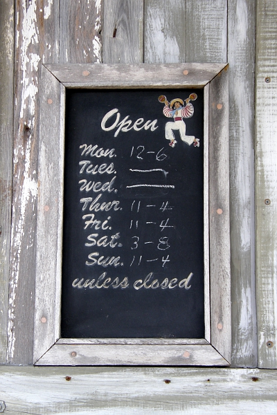 Sign listing a store's opening hours
