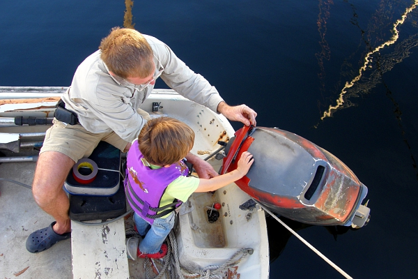 Father and son applying red tape to an old outboard motor