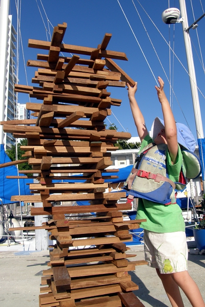 Boy adding piece of wood to the top of a tower.