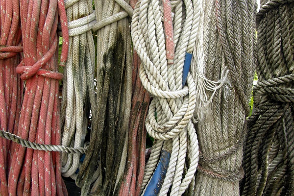 Weathered dock lines hanging on a stand.