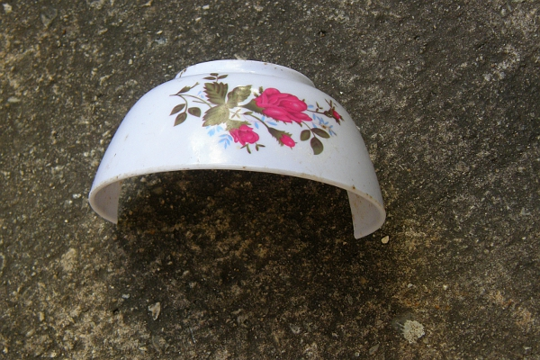 Broken bowl on concrete pavement.
