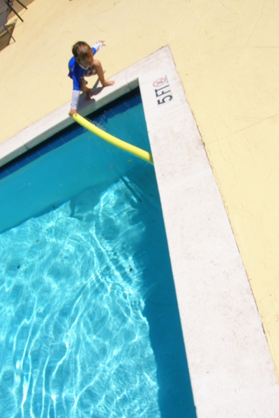 Boy picking up yellow noodle from the edge of a swimming pool.