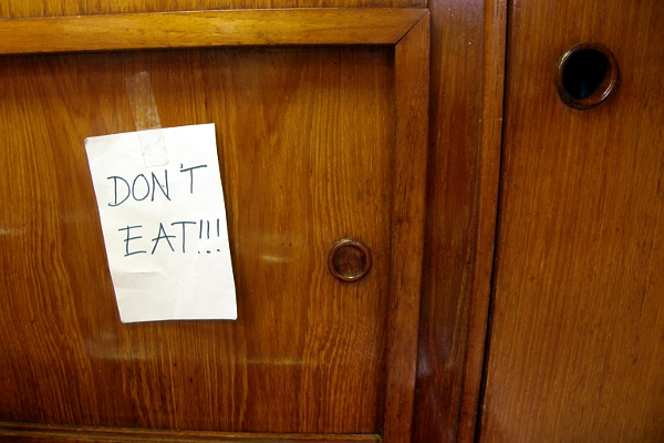 Don't Eat note stuck to kitchen cabinet.