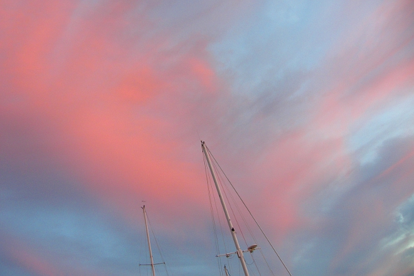 Looking up to the top of sailboat masts at beautiful sunset sky