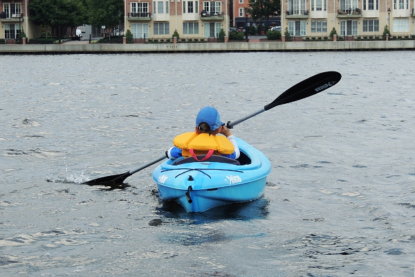 Boy paddling in kayak.