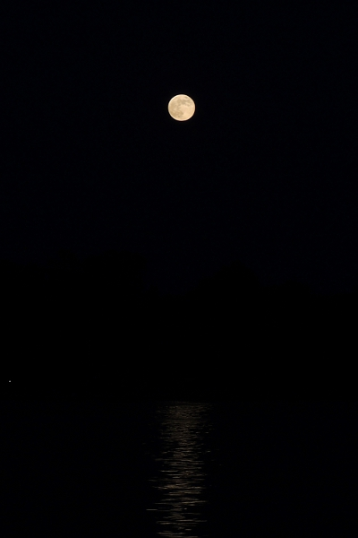 Full moon with moonlight reflecting over water