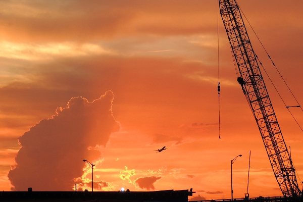 Crane, airplane, and cloud in sunset over Miami River