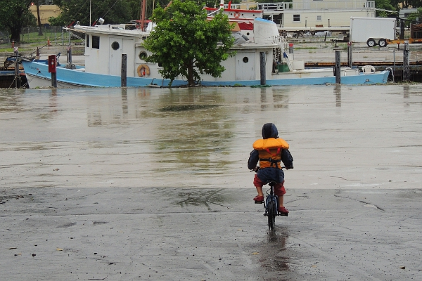 boy riding bicycle in marina with life vest and rain coat on