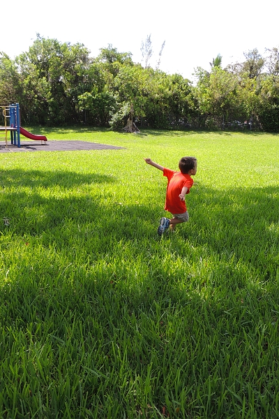 boy running in the grass by a playground