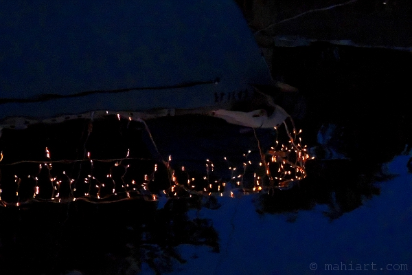 Reflection of boat at night with Christmas lights