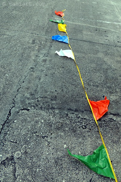 String of plastic flags on concrete pavement