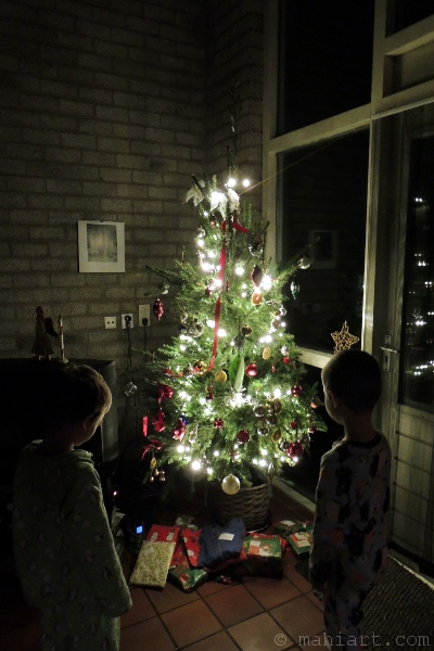 Boys looking at presents under the Christmas tree
