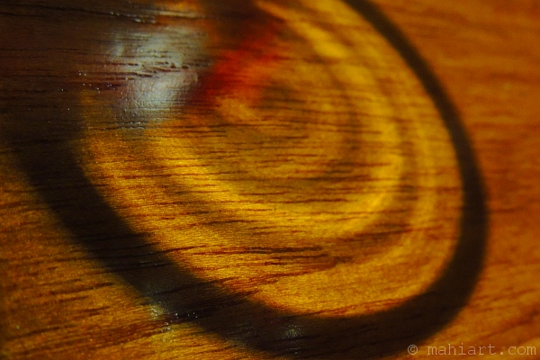 Shadow cast by a glass of red wine on a wood table