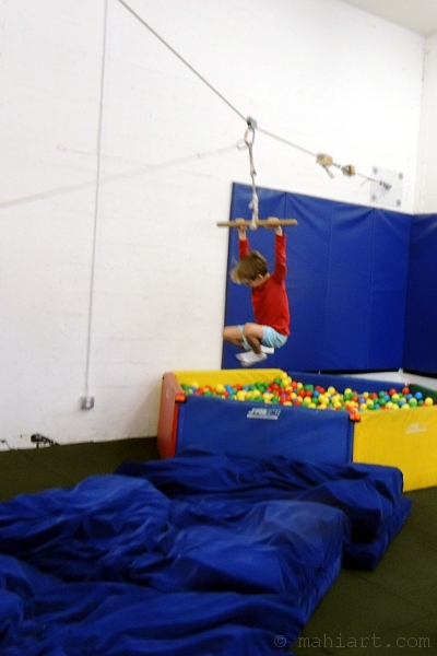 Boy at colorful indoor playground zip line