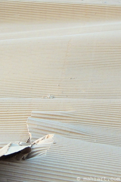 Closeup of an undulating sheet of corrugated cardboard, looking like a desert landscape.