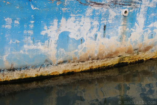 Closeup of weathered fishing boat hull and its reflection in the water.