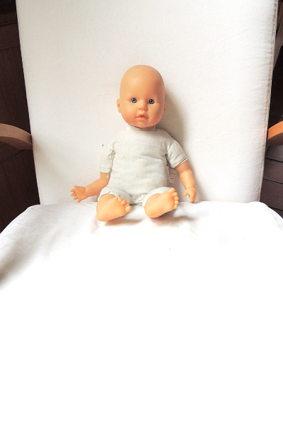 A baby doll, sitting in a white living room chair