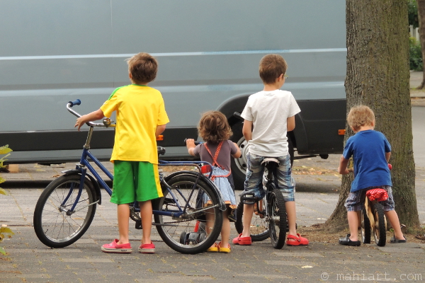 Four kids standing on the sidewalk with their bicycles
