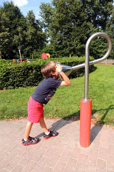 Boy shouting into a playground sound fixture