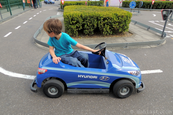 Child in battery operated car in the middle of a playground road