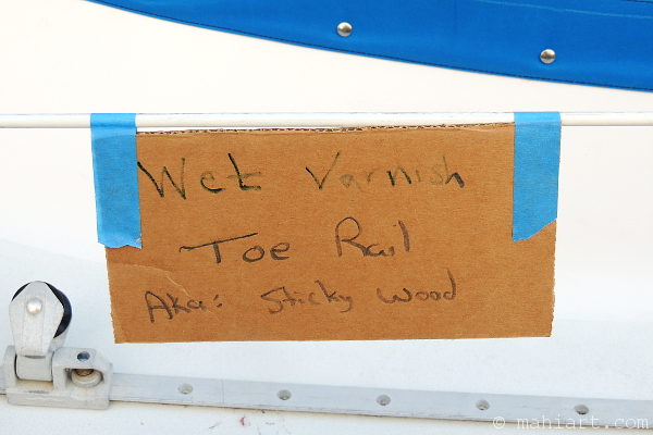 Note on sailboat's lifelines that warns of wet varnish aka sticky wood