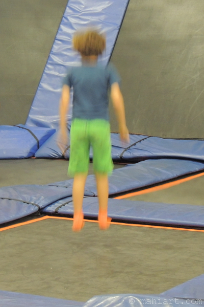 Blurry picture of a boy jumping on trampolines at Sky Zone