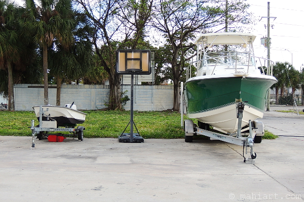 Basketball goal between two boats on trailers