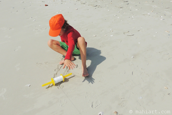 Boy on the beach, reaching for a kite spool that has accidentally slipped out of his hands