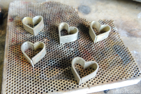 Sterling silver hearts on soldering block, ready to be made into heart pendants.